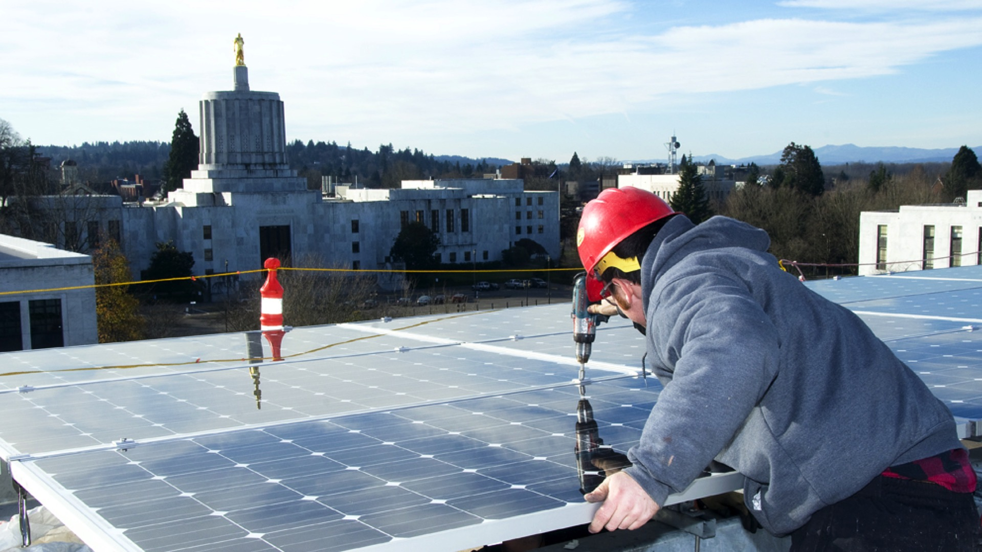 man installing solar panels on top of building