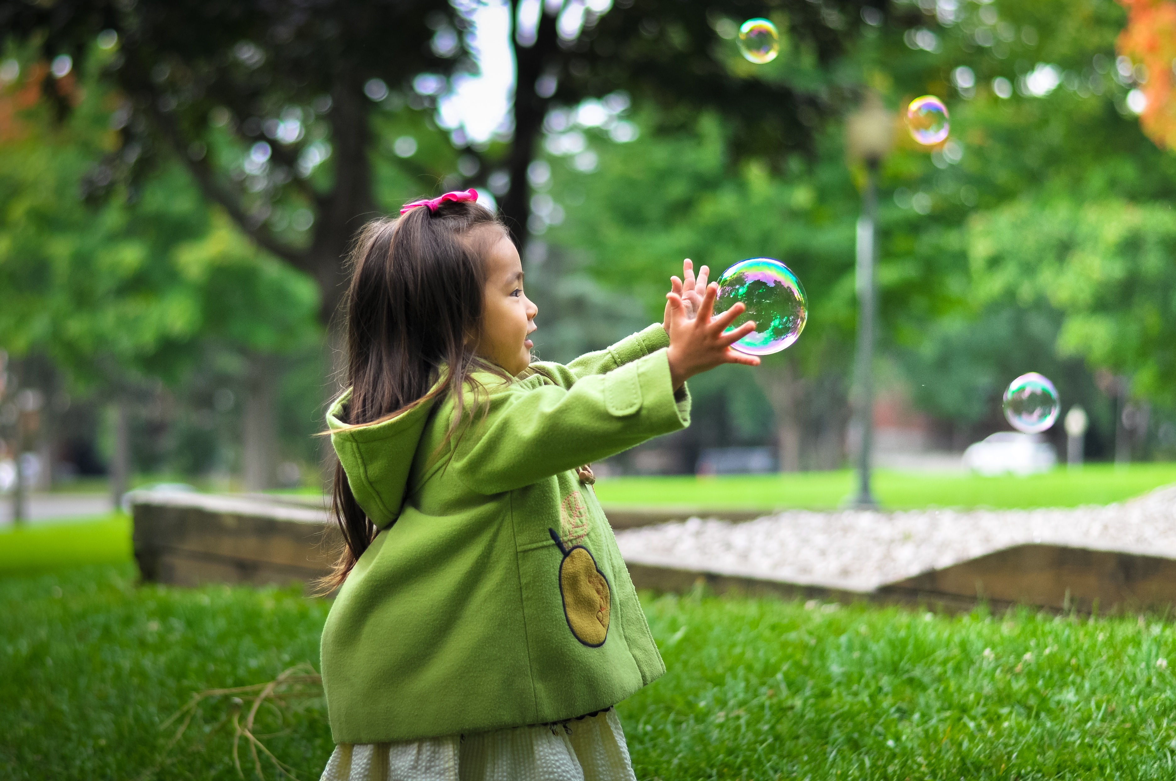 child playing with bubbles in grass