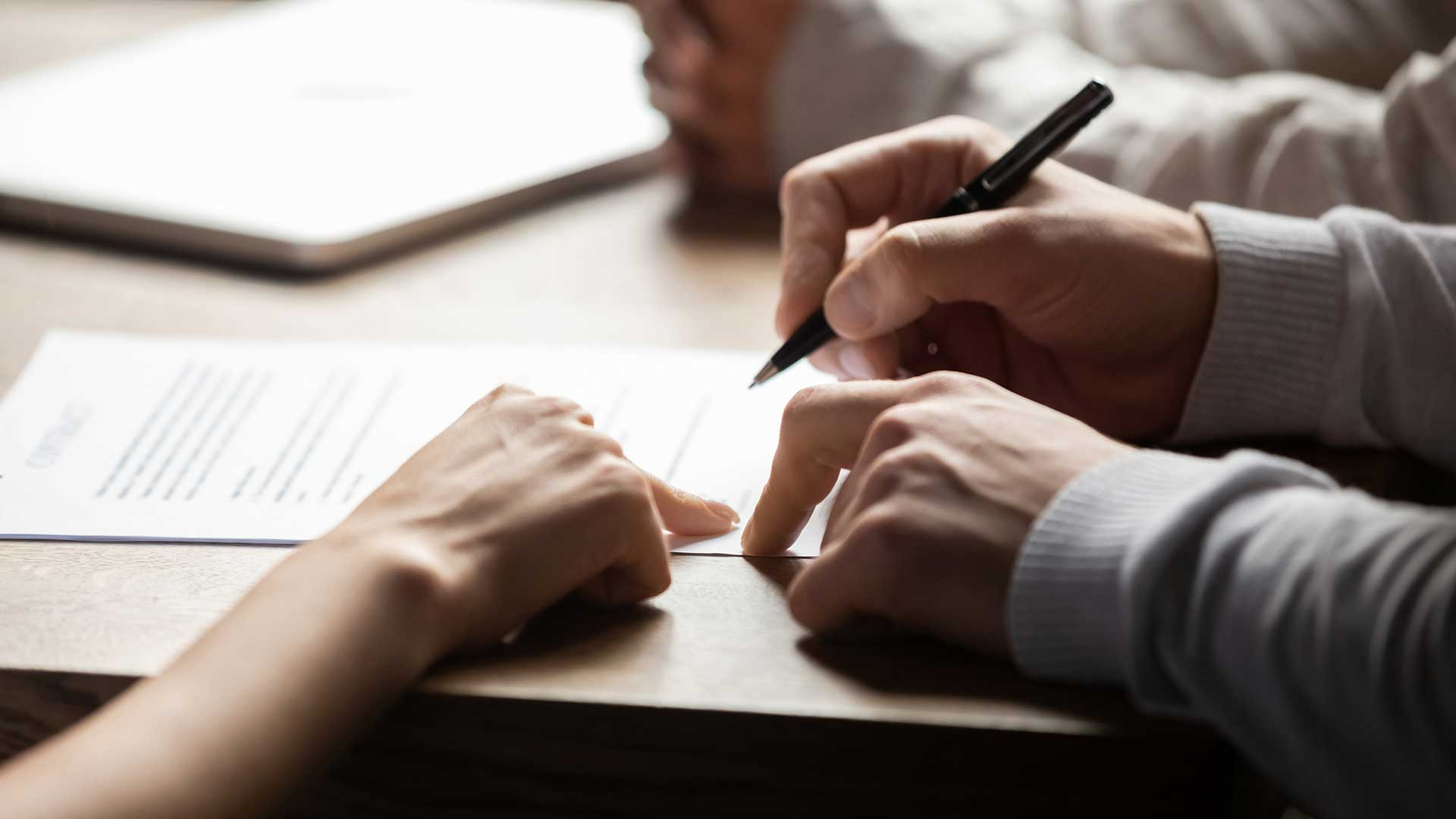 closeup of hands signing documents