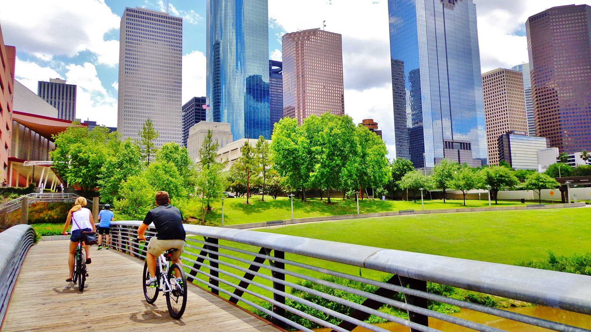 bicyclists cross bridge in park with houston skyline in background