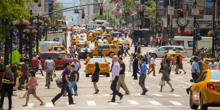busy intersection with pedestrians and cars in new york