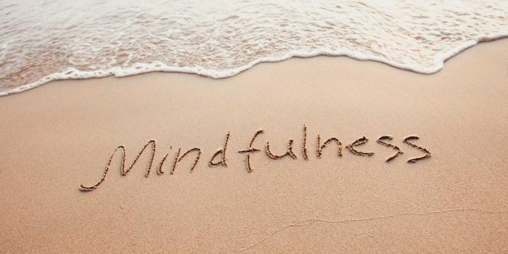 Mindfulness written in sand at beach